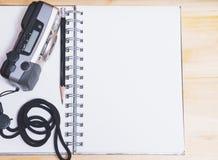 Anteckningsbok med den kompakta kameran för gammal film och den svarta blyertspennan Arkivfoto