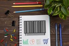 Anteckningsbok med en anmärkningsbarcodeprodukt på kontorstabellen med t arkivfoto