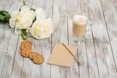 Anteckningsbok med en blyertspenna bredvid exponeringsglas av cappuccino och kakor på vit träbakgrund placera text Royaltyfria Bilder
