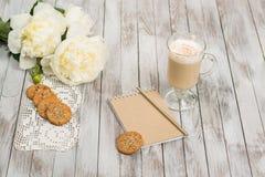 Anteckningsbok med en blyertspenna bredvid exponeringsglas av cappuccino och kakor på vit träbakgrund placera text Royaltyfria Foton