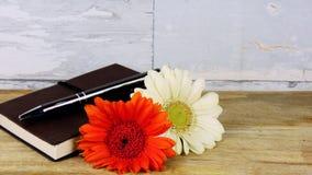 Anteckningsbok med en blyertspenna och blommor royaltyfri fotografi