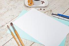 Anteckningsbok med en inskrift, kaffe med baglar, pennor och penci Royaltyfri Bild