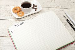 Anteckningsbok med en inskrift, kaffe med baglar, pennor och penci Arkivbilder