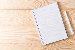 Anteckningsbok med en penna på en träbakgrund royaltyfria bilder