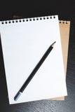 Anteckningsbok med en svart blyertspenna på en trätabell royaltyfria foton