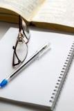 Anteckningsbok med exponeringsglas och penna på tabellen Royaltyfri Bild