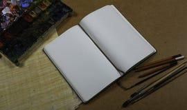 Anteckningsbok med färgblyertspennor Royaltyfri Fotografi