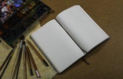 Anteckningsbok med färgblyertspennor Arkivbild