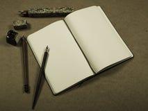 Anteckningsbok med färgblyertspennor Arkivfoto