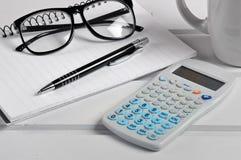 Anteckningsbok med glasögon, räknemaskinen och pennan Arkivfoton
