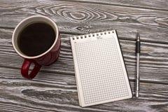 Anteckningsbok med kaffe på en trätabell Arkivfoto