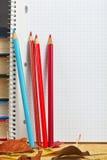 Anteckningsbok med kulöra blyertspennor och höstsidor Royaltyfri Fotografi