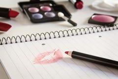 Anteckningsbok med kyssen och makeup Royaltyfria Bilder