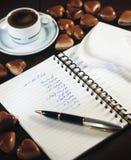 Anteckningsbok med listan för shopping för bröllopparti bredvid en kopp kaffe- och chokladhjärtastilleben arkivfoto
