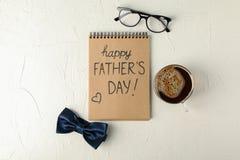 Anteckningsbok med lycklig faderdag för inskrift, den blåa flugan, koppen kaffe och exponeringsglas på vit bakgrund royaltyfri foto