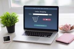 Anteckningsbok med online-shopping på skärmen i kontoret Arkivfoto