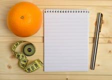 Anteckningsbok med orange frukt fotografering för bildbyråer