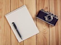 Anteckningsbok med penn- och tappningkameran på träskrivbordet Top beskådar royaltyfria bilder