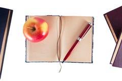 Anteckningsbok med pennan och äpplet royaltyfri foto