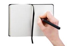 Anteckningsbok med pennan och handen Fotografering för Bildbyråer