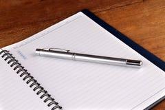 Anteckningsbok med pennan på gamla trätabeller arkivbilder