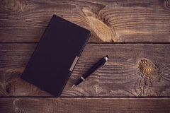 Anteckningsbok med pennan på trätabellen Fotografering för Bildbyråer