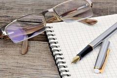 Anteckningsbok med reservoarpennan och glasögon på tabellen Fotografering för Bildbyråer