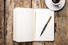 Anteckningsbok med reservoarpennan och kopp av espresso Arkivfoton