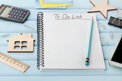 Anteckningsbok med som gör listan och olika kontorshjälpmedel på det blåa lantliga skrivbordet Arkivfoto
