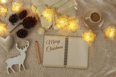 Anteckningsbok med text: GLAD JUL och kopp av cappuccino över hemtrevlig och varm pälsmatta Top beskådar royaltyfri bild