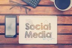 Anteckningsbok med text inom socialt massmedia på tabellen med kaffe, folkhop royaltyfri fotografi