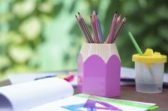Anteckningsbok och ask av blyertspennor Arkivfoto