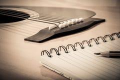 Anteckningsbok och blyertspenna på gitarrbakgrund Arkivfoton