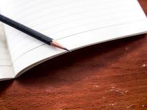 Anteckningsbok och blyertspenna på tabellen Royaltyfri Bild