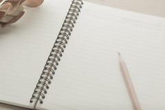 Anteckningsbok och blyertspenna på tabellen Arkivbilder