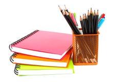 Anteckningsbok och blyertspennor på vit bakgrund Royaltyfri Fotografi