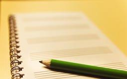 Anteckningsbok och en grön blyertspenna på gul bakgrund kontorsproblemläge som löser tema arkivfoto