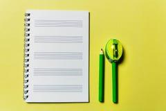 Anteckningsbok och en grön blyertspenna och vässare på gul bakgrund kontorsproblemläge som löser tema royaltyfri bild