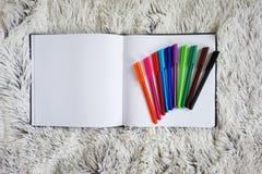 Anteckningsbok och färgade pennor Arkivbild