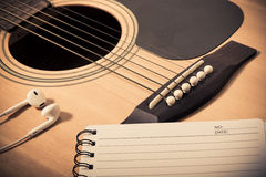 Anteckningsbok och headphone på gitarrbakgrund Arkivfoton