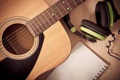 Anteckningsbok och headphone på träbakgrund med gitarren Arkivfoton