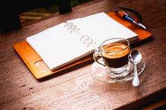 Anteckningsbok- och kaffekopp på gammal träbakgrund, affärsconce Royaltyfri Bild