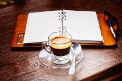 Anteckningsbok- och kaffekopp på gammalt trä Royaltyfria Foton