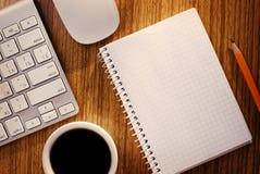 Anteckningsbok och kopp kaffe nära datortangentbordet Arkivbilder