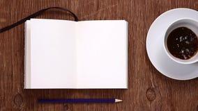 Anteckningsbok och kopp som fylls med kaffe arkivfilmer