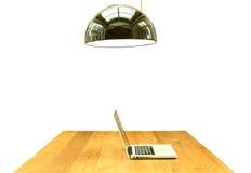 Anteckningsbok och lampa för dator för kontorsskrivbord på den isolerade trätabellen Royaltyfri Bild