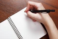 Anteckningsbok och penna i hand bakgrund isolerad white Fotografering för Bildbyråer