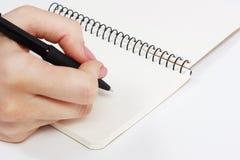 Anteckningsbok och penna i hand bakgrund isolerad white Royaltyfri Foto