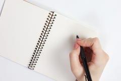 Anteckningsbok och penna i hand bakgrund isolerad white Royaltyfria Bilder