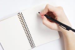 Anteckningsbok och penna i hand bakgrund isolerad white Arkivbild